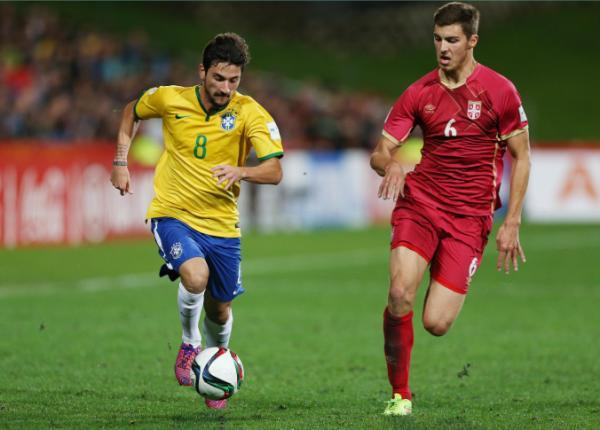 Brazil's Boschilia, left, takes the ball as Serbia's Srdan Babic follows during the U20 soccer World Cup final in Auckland, New Zealand, Saturday, June 20, 2015. (AP Photo/David Rowland)