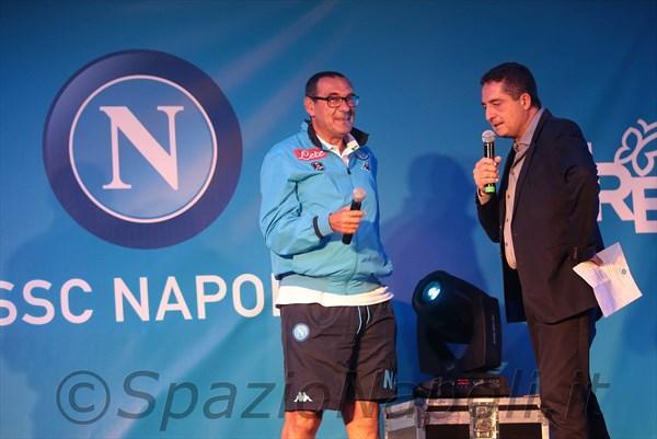 """La Presentazione - """"Sono emozionato da 20 giorni, non da stasera. Pensavo di essere nato a Napoli casualmente, ma non è così. Mi sono emozionato al San Paolo già da avversario, figuriamoci da padrone di casa. A scuola l'unico tifoso del Napoli ero io. Sono andato a vedere anche partite di Coppa dei Campioni a Napoli nel periodo di Maradona"""".  Si presenta così Maurizio Sarri, nella piazza di Dimaro, davanti al suo nuovo pubblico. L'emozione è tanta, così come la consapevolezza di avercela fatta. L'allenatore nato a Napoli, tifoso del Napoli, che ha viaggiato per tutta Italia facendo tanta, tanta gavetta, realizza il suo sogno di allenare la squadra che da sempre gli fa battere il cuore. Tanto, forse troppo scetticismo nei suoi confronti all'arrivo, complice il fatto di non provenire da una società blasonata e di non aver allenato ancora in grandi piazze. I tifosi, ancora sotto l'incantesimo Benitez, non sorridono come dovrebbero e lo scetticismo è ancora tanto. Un inizio per niente felice rende il tutto ancora peggiore ma la reazione e la consapevolezza che sia nato un grande Napoli, che sia nato un nuovo progetto, riportano i tifosi al San Paolo a viaggiare sulle stesse frequenze d'onda della squadra. Ed è anche merito, soprattutto, di quest'uomo in tutta, emozionato al momento della presentazione, così come ogni volta che scende in campo, in casa o in trasferta, coi colori azzurri stampati nel cuore."""